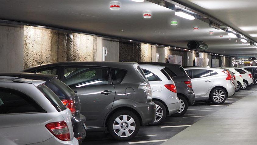 Parkeringshus med parkerade bilar på rad